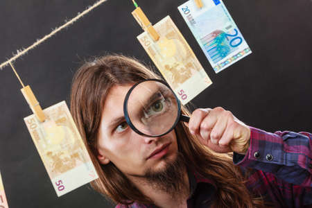 man laundry: Currency exchange concept. Man worker check verify money cash. Payment hang on laundry line. Guy with loupe.