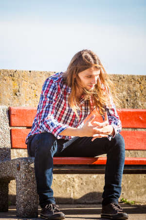 man with long hair: Man long hair alone on bench, lost in thought, is concerned and stressed about events in his life. Unemployment depression concept