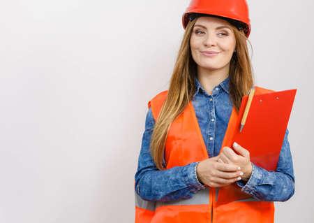 Woman construction worker builder structural engineerin in orange vest red hard helmet holds pen file pad. Safety in industrial work. Studio shot