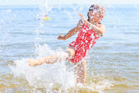young girl bath: Little girl child having fun in ocean. Kid and woman bathing splashing sea water. Summer vacation holiday relax.