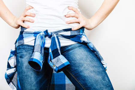checked shirt: Closeup of human hips with checked shirt wearing jeans. Stock Photo
