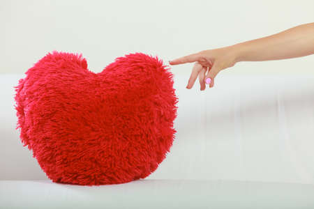 red sofa: Human hand touching red heart shape pillow on sofa couch. Valentines day love.