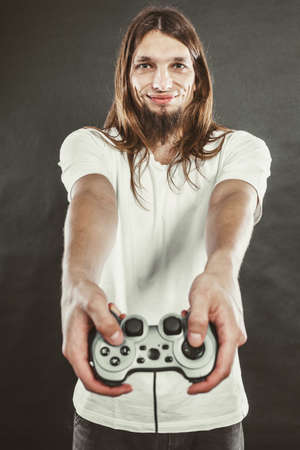 xbox: Playing games. Young smiling cheerful man play on console xbox playstation. Guy with pad joystick.