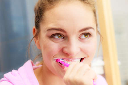 cleanliness: Woman brushing cleaning teeth. Girl with toothbrush in bathroom. Oral hygiene.