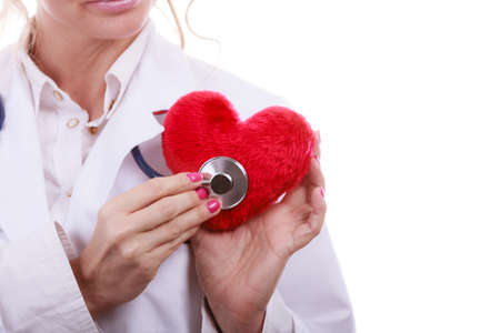 the cardiologist: Medical examination of cardiology. Cardiologist with heart and stethoscope. Female doctor in white uniform makes measurement heartbeat. Isolated on white.