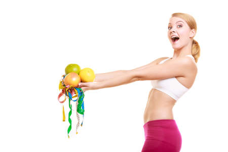 measures: Happy joyful young woman girl holding grapefruits and tape measures. Slimming and dieting. Healthy lifestyle nutrition concept. Isolated on white. Stock Photo