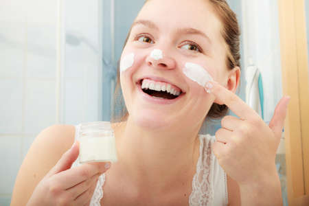 skincare: Happy young woman applying cleansing moisturizing skin cream on face. Girl taking care of dry complexion layering moisturizer. Skincare.
