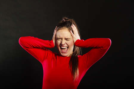 hands covering ears: Stressed young woman not listening covering ears with hands screaming in studio on black. Stock Photo