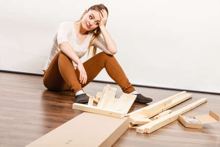 self assembly: Worried helpless woman assembling wooden furniture. DIY enthusiast. Young girl doing home improvement. Stock Photo