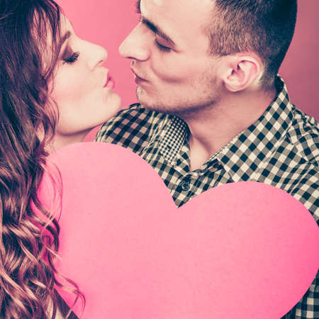 romantic couple kissing on valentines day. happy joyful man and woman holding heart symbol looking in each other eyes. love concept.