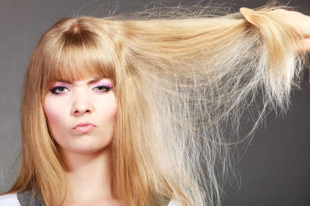 dry hair: Haircare. Blonde woman with her damaged dry hair angry face expression gray background