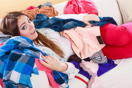 Happy woman lying on sofa couch in messy living room. Young girl surrounded by many stack of clothes. Disorder and mess at home. Stock Photo