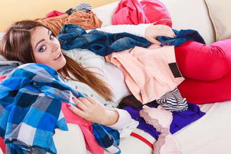 habitacion desordenada: Mujer feliz que miente en el sofá cama en el salón desordenado. Chica joven rodeada por muchos pila de ropa. El desorden y el caos en el país.