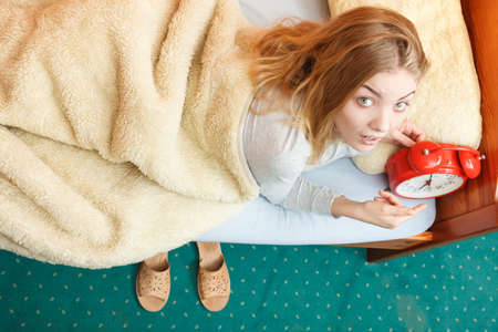 oversleep: Unhappy woman waking up in bed with alarm clock. Young girl in the morning.