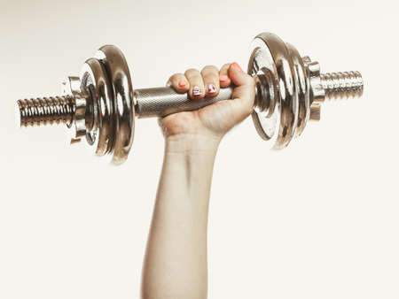 gaining: Closeup of arm hand strong human lifting dumbbells weights. Fit person exercising gaining building muscles. Fitness and bodybuilding. Stock Photo