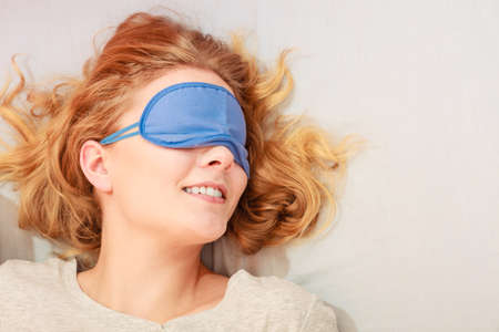 blindfold: Tired woman sleeping in bed wearing blindfold sleep mask. Young girl taking nap.