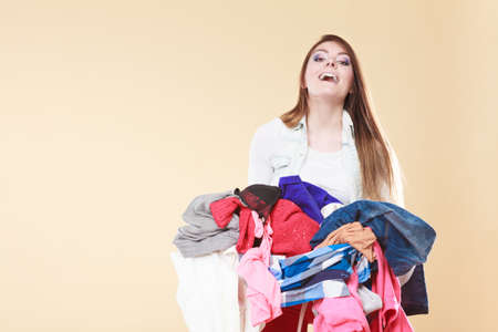 pile of clothes: Happy young woman carrying stack pile of dirty laundry clothes. Girl cleaning tidying in studio. Stock Photo