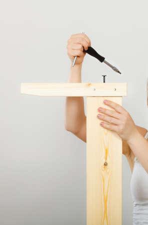 enthusiast: Human hand assembling wooden furniture using screwdriver. DIY enthusiast. Home improvement. Stock Photo