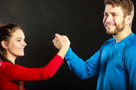 clasping: Happy friends young man and woman clasping shaking hands. Handshake greeting gesture in studio on black. Stock Photo