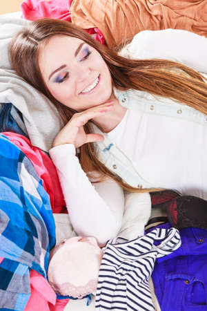 mess: Portrait of happy glad young woman girl lying on stack of clothes. Disorder and mess.