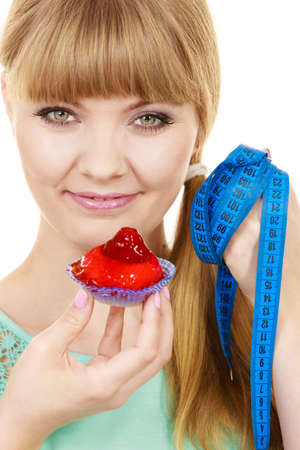 overeat: Woman smiling girl with blue measuring tape holds in hand cake cupcake. Weight loss dieting or sweet food and happiness concept.