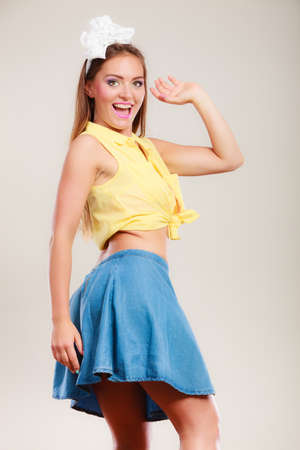 hairband: Alluring seductive pretty pin up girl wearing hairband bow and skirt. Attractive gorgeous young retro woman dancing on table. Stock Photo