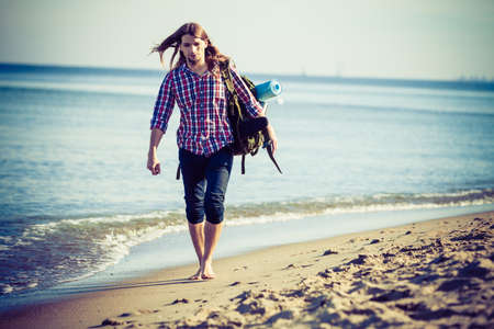 tramping: Man hiker backpacker walking with backpack on sea shore at sunny day. Adventure, summer, tourism active lifestyle. Young long haired guy tramping