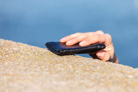 Man thief finding wallet on sea shore taking stealing it. Leaving belongings unattended and risk of theft