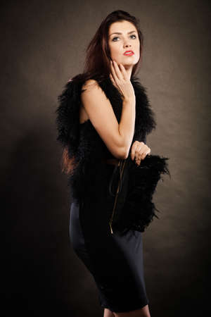 feather boa: Party celebration carnival concept.  Magnificent long hair woman wearing black evening dress feather boa holds handbag in hand on dark Stock Photo