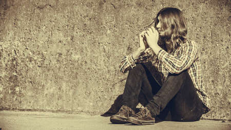 Man bearded long hair sitting sad alone by grunge wall outdoor. Unemployment depression or sadness concept.
