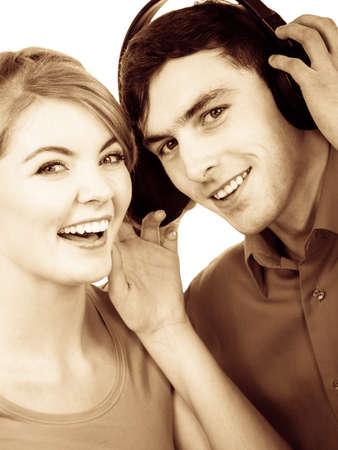 personas escuchando: Par de dos amigos con grandes auriculares escuchando música mp3 juntos. Mujer alegre feliz y el hombre en blanco. La gente de ocio concepto de la felicidad. foto filtrada