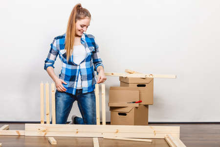 self assembly: Woman moving in assembling furniture at new home. Young girl arranging apartment house interior and unpacking boxes. DIY.