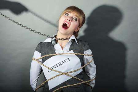 Scared businesswoman bound by contract terms and conditions.  Afraid and helpless woman tied to chair become slave. Human hand hold chain and has power over girl. Business and law concept. Stock Photo