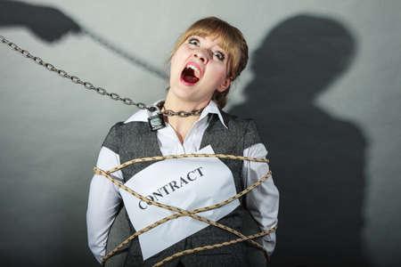 gefesselt: Scared Geschäfts von Vertragsbedingungen gebunden. Angst und hilflose Frau auf Stuhl geworden Slave gebunden. Human hand hold Kette und hat Macht über Mädchen. Wirtschaft und Recht-Konzept.