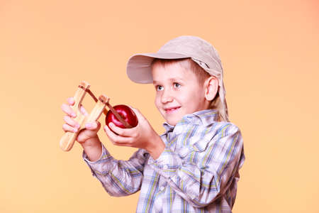prankster: Nature and free time prankster little boy. Child have fun with  wooden sling shot and fruit hold apple. Stock Photo