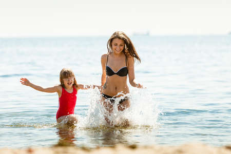 bathing women: Little girl child and mother running having fun in ocean. Kid and woman bathing in sea splashing water. Summer vacation holiday relax. Stock Photo
