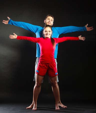 sportwear: Portrait of smiling woman and man in sportwear posing in studio on black. Happy joyful couple. Good relationship.