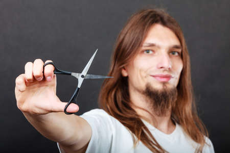trimmers: Hairdresser and barber. Long haired handsome man hairstylist with scissors. Young male showing trimmers.