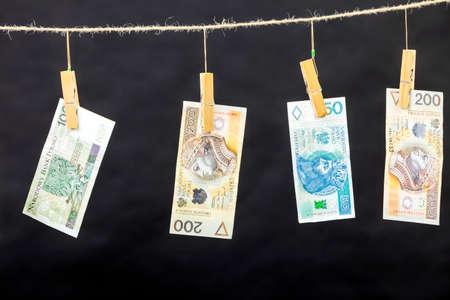 laundry line: Banknotes cash money hang on laundry line on black background. Stock Photo