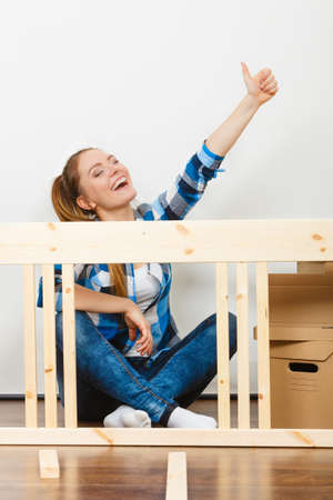 self assembly: Woman moving into new apartment house assembling furniture. Young girl with thumb up arranging interior and unpacking boxes. Success and achievement. Stock Photo