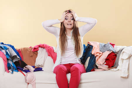 Desperate helpless woman sitting on sofa couch in messy living room with hands on head. Young girl surrounded by many stack of clothes. Disorder and mess at home.