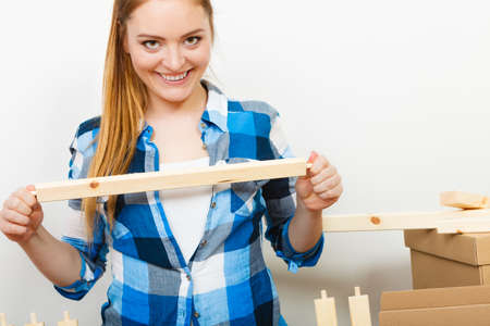 self assembly: Woman assembling wooden furniture. DIY enthusiast. Young girl doing home improvement.