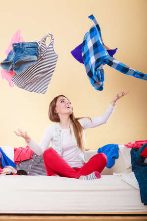 messy: Happy woman sitting on sofa couch in messy living room throwing clothes. Young girl surrounded by many stack of clothing. Disorder and mess at home.