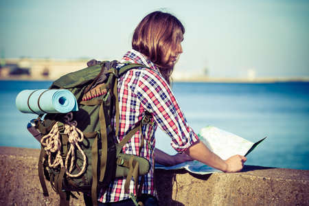 tramping: Man hiker backpacker with backpack by seaside reading map searching looking for direction guide. Adventure, tourism active lifestyle. Young long haired guy tramping