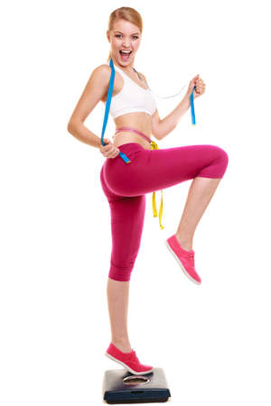clenching fists: Slimming and weight loss success. Happy young woman girl measuring with tape measures on weighing scale clenching fists. Healthy lifestyle concept. Isolated on white. Stock Photo