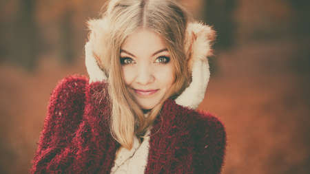 fall winter: Portrait of pretty attractive fashionable woman in fall forest park. Gorgeous young girl in earmuffs and maroon sweater pullover. Autumn winter fashion. Instagram filter.