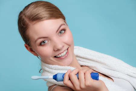 bad breath: Pretty young girl with brush cleaning white using toothpaste. Happy woman cleaning her oral cavity caring about dental health holding toothbrush.