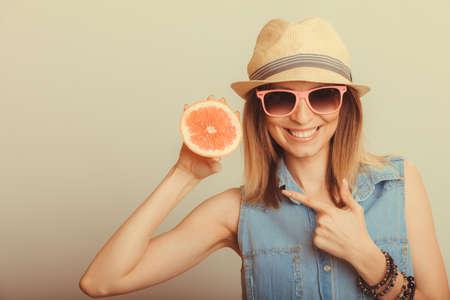 pomelo: Feliz contenta turística de la mujer con sombrero de paja y gafas de sol que señalan en los cítricos de pomelo. alimento de la dieta saludable. Vacaciones de verano concepto de vacaciones. Foto de archivo