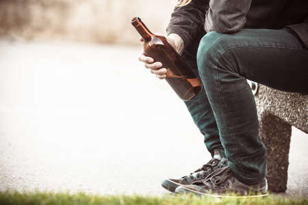 social problems: Man depressed with wine bottle sitting on bench outdoor. People abuse and alcoholism problems.