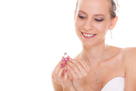admiring: Joyful happy bride showing and admiring engagement ring. Excited woman in white wedding dress isolated on white background. Stock Photo